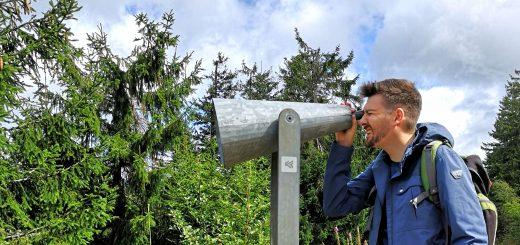 Mann schaut durch eine Fernrohr im Wald